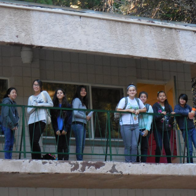Students stand outside their rooms early in the morning, ready to explore the vast outdoors.