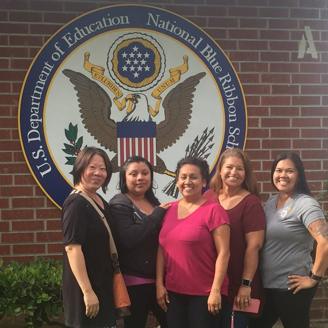 Volunteer mothers pose in front of the school's new badge of honor: The National Blue Ribbon!