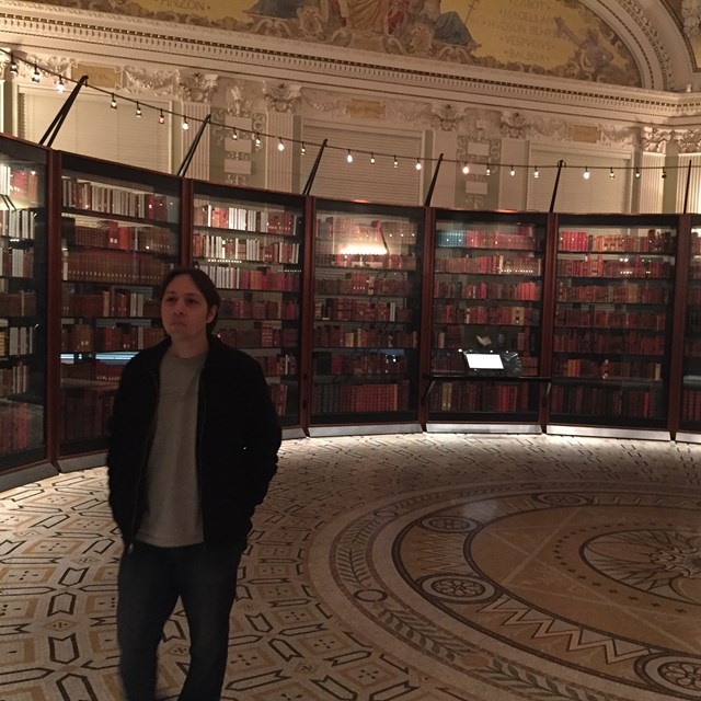Look at this student standing in a vast library!