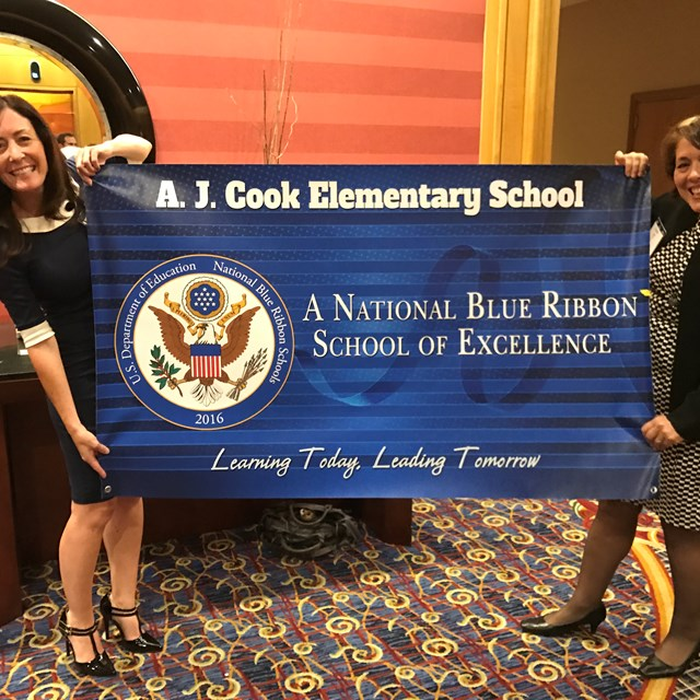 Teachers holding up the Blue Ribbon Award proudly given to Cook Elementary.